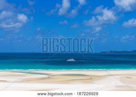 White cruise liner on turquoise blue waters of Coral sea on sunny day. Summertime vacation holiday background. Whitsundays Whitehaven beach. Queensland Australia