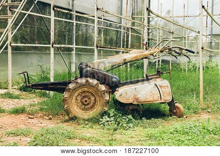 Old rusty garden power tiller in greenhouse. Vintage hand motor cultivator on green grass