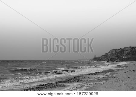Beautiful tide on the Black Sea beach sky and sea sand and cliffs on black and white photo