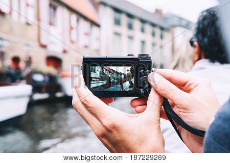 Tourist's hands holding digital photo camera on vacations taking picture of canal in Bruges Belgium. View on city from boat. Travel Europe. Belgian traditional blurred architectural background