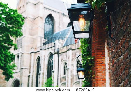 Details of a historic building in Bruges Belgium Europe. Belgian traditional architecture. Close-up of lamp with blurred architectural background.