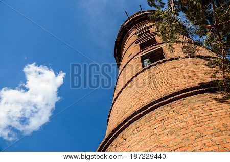 Abandoned water tower against a clear sky and clouds. Reminds the ancient castle.