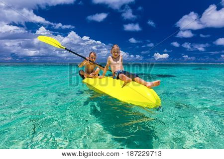 Two young shirtless caucasian boys kayaking at tropical sea on yellow kayak