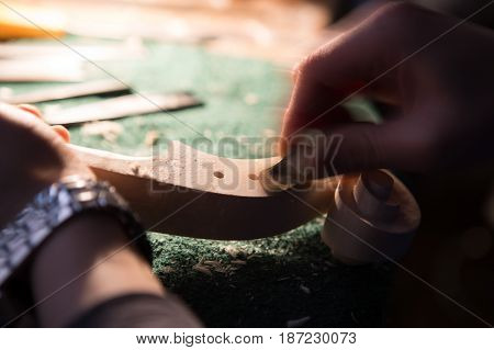 craftsman violin maker carving a neck in his laboratory