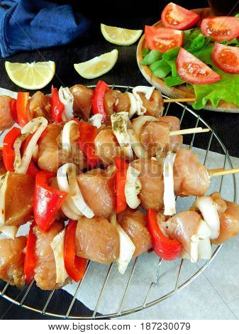 Raw meat with vegetables on skewers lying on the grill lattice. Processed product for shashlik cooking