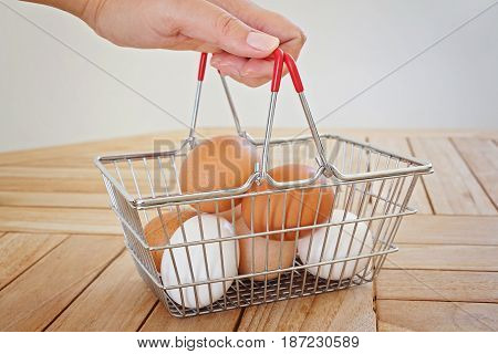 Woman's hand holds a metal shopping basket with chicken eggs. A few fresh natural eggs in a metal basket