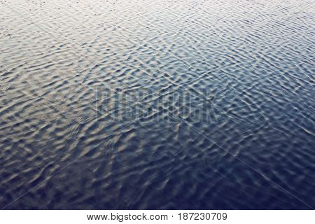 Water surface with ripples at sunset. Ripple texture.