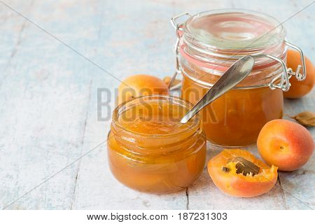 Freshly cooked dessert. Ripe apricots and two jars of jam on a light wooden background.