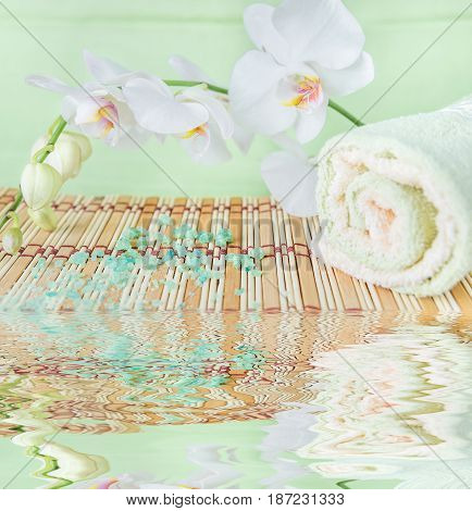 Spa concept: bath towels and bath salt on a natural mat and a branch of white orchid on a green background reflected in a water surface with small waves