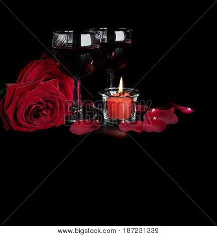 Valentine's Days concept: two glasses of red wine two red roses and a burning red candle isolated on a black background