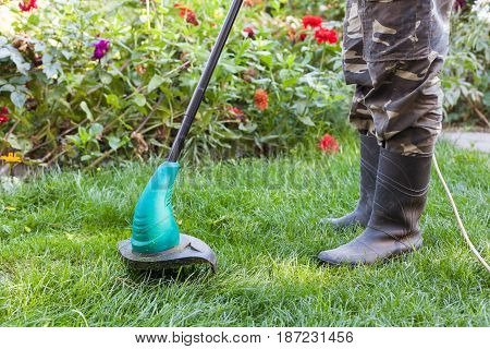 Man mowing grass lawn mower on the background of flower beds
