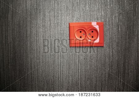 Red socket outlet on silver wall. Electricity background concept.