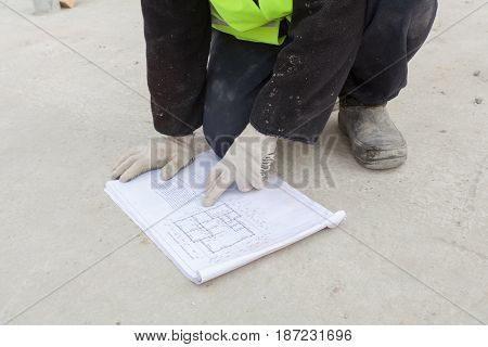 Frame house construction. Worker looks on scheme of arrangement of wall panels