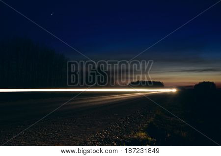 Night highway landscape and headlight of car under dark blue sky.