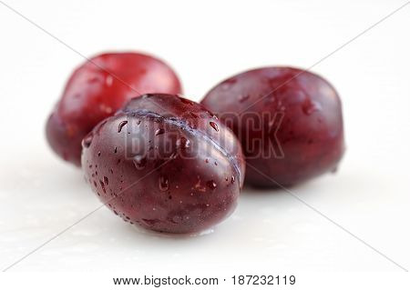Red plums with water drops on white background