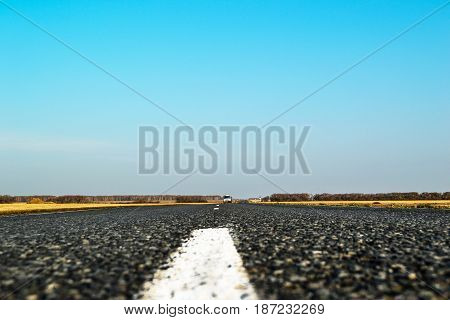 Truck on empty road in country side landscape marking strip