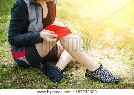 Woman Placing Kinesiology Tape On Knee.