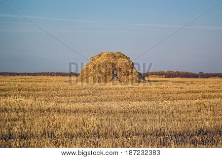 Happy man and hay stack in the wheat field.