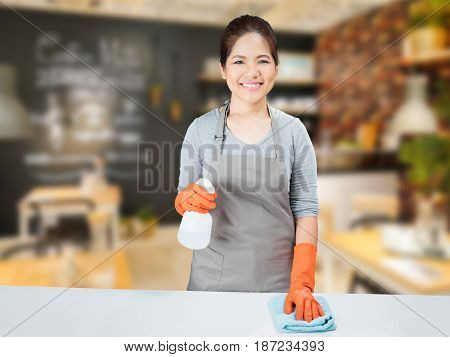 asian housewife sweeping on grey table in kitchen