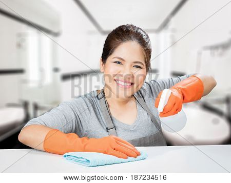 asian housewife sweeping on table wearing gloves