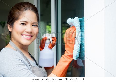 asian housewife or housekeeper cleaning on glass window