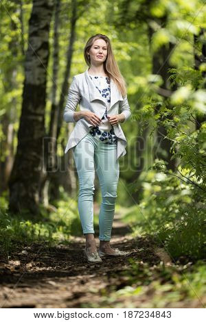 Happy young woman walking in the summer park