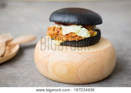 Black burger with Chicken and lettuce on a cutting board