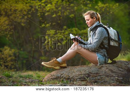Active healthy woman hiking in beautiful forest. Portrait of happy young woman resting of forest clearing and leading notes on nature writing diary during hike holidays.