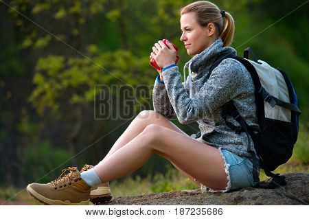 Active healthy woman hiking in beautiful forest. Portrait of happy smiling young woman with cup of tea resting of forest clearing during hike holidays.