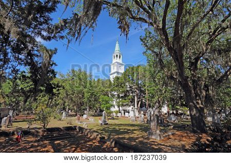 Spire and graveyard framed by Spanish moss-covered trees at the parish church of St. Helena in the historic district of downtown Beaufort South Carolina