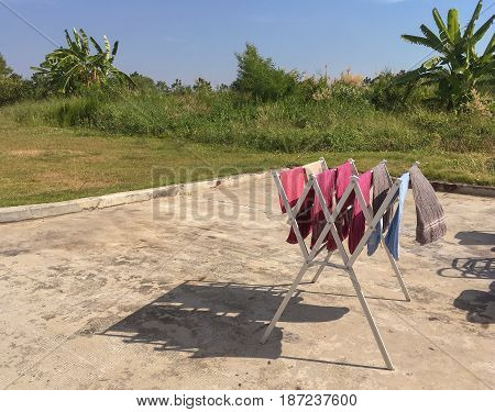 Colorful wet towels are being hung on bar for drying.