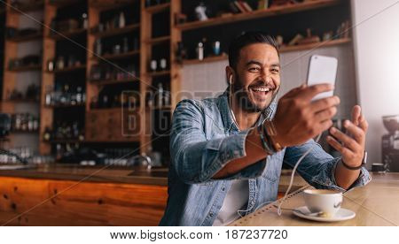 Happy young caucasian man sitting at cafe making video call from his mobile phone. Caucasian male at coffee shop having a videochat on smart phone.
