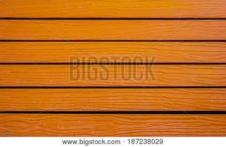Texture of orange color stripe wooden lumber wall. Bright color use for background.