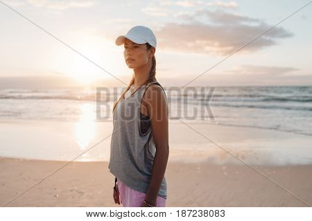 Shot of fit young woman in sportswear standing on the beach and looking away. Beautiful fitness model on the sea shore in morning.