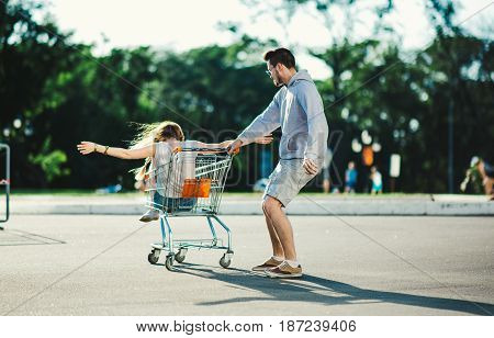 Young couple in love having fun on the street with a shopping cart from a supermarket