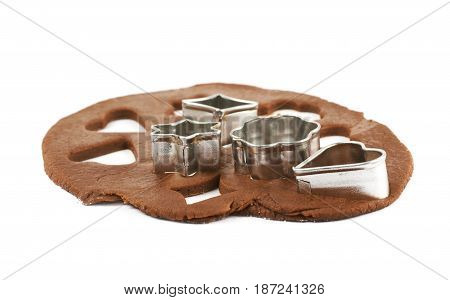 Rolled up thin layer of cookie dough with a pile of cookie cutters over it, composition isolated over the white background