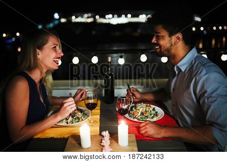 Beautiful couple in love having romantic dinner at night on rooftop