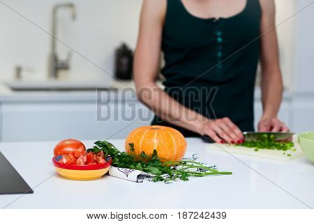 Woman  cooking in the kitchen. Tomato, pumpkin in table. Vegetarian and healthily cooking concept