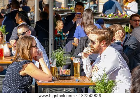 Young Businessman And Businesswomen Drinking At A Packed Outdoor Bar In Canary Wharf