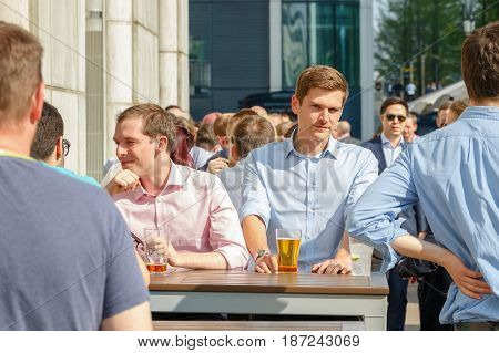 A Young Businessman Drinking With His Colleagues At A Packed Outdoor Bar In Canary Wharf
