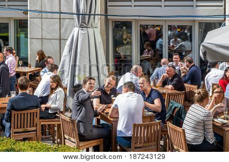 An Outdoor Bar In Canary Wharf Packed With People Drinking And Chatting Business