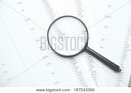 Business concept with magnifier and financial documents.