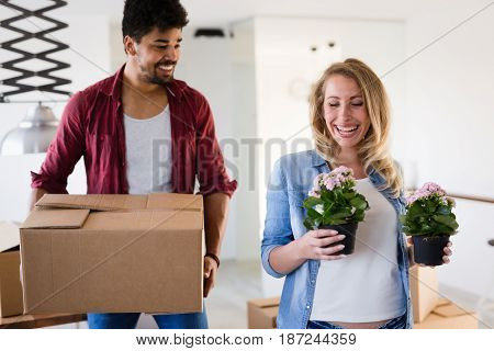 Young married couple Moving in new home and unpacking carboard boxes