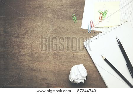 notebook clippapers and pen on wooden table
