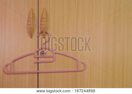 Hanger is being hanged on the door in front of the key hole.
