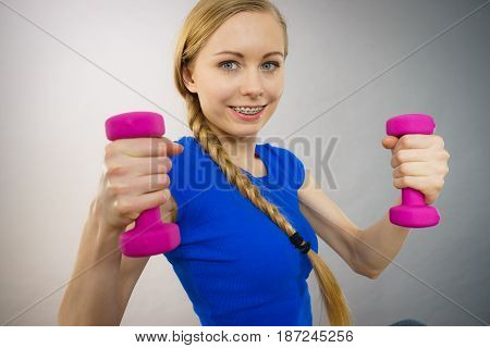 Teenage young woman working out at home with small light dumbbells. Training at home being fit and healthy.