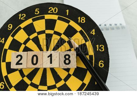 New year planning target concept with wooden blocks number 2018 on dart board pencil and note paper.
