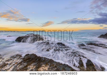 Ocean tide cascading over the rocks during sunrise at Currumbin Rock, Gold Coast