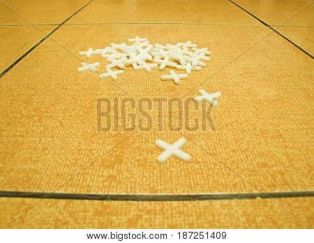 crosses for laying tiles on a background of orange tiles