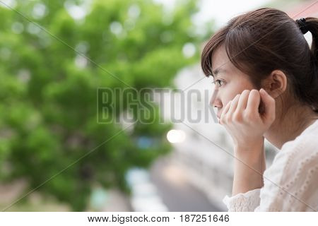 woman feel depression and look somewhere next the balcony
